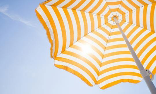 Orange and white stripped beach umbrella with sun