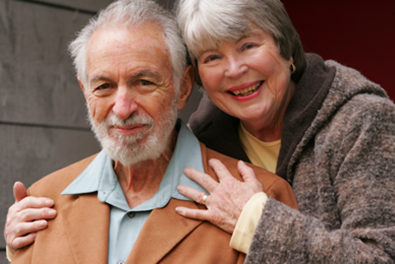 Elderly woman hugging elderly mans shoulders from behind