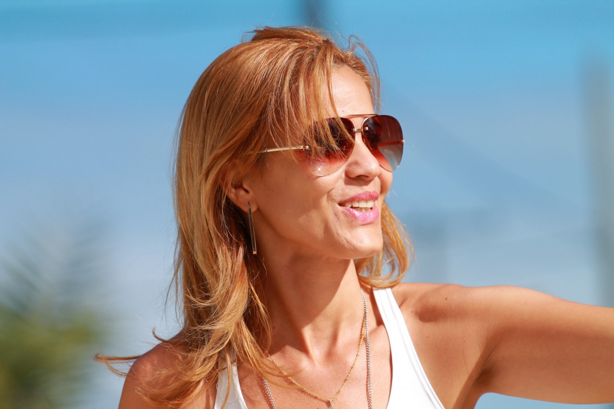 Woman in the sun wearing sunglasses smiling