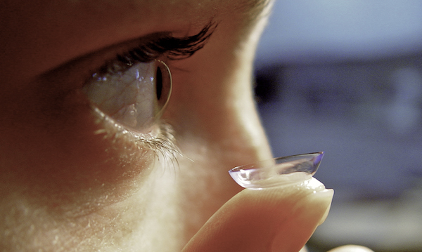 Person putting contact lens in their eye