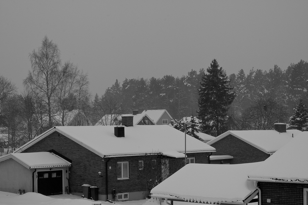 Snowy residential home roof tops on a dark winter day