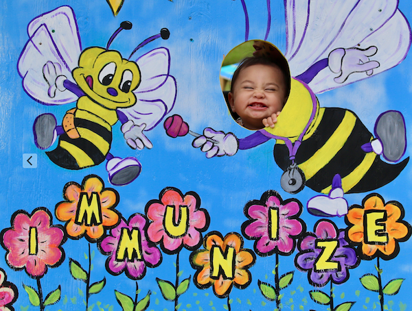 child with face in plywood cutout that has bumble bees and the word immunize on it