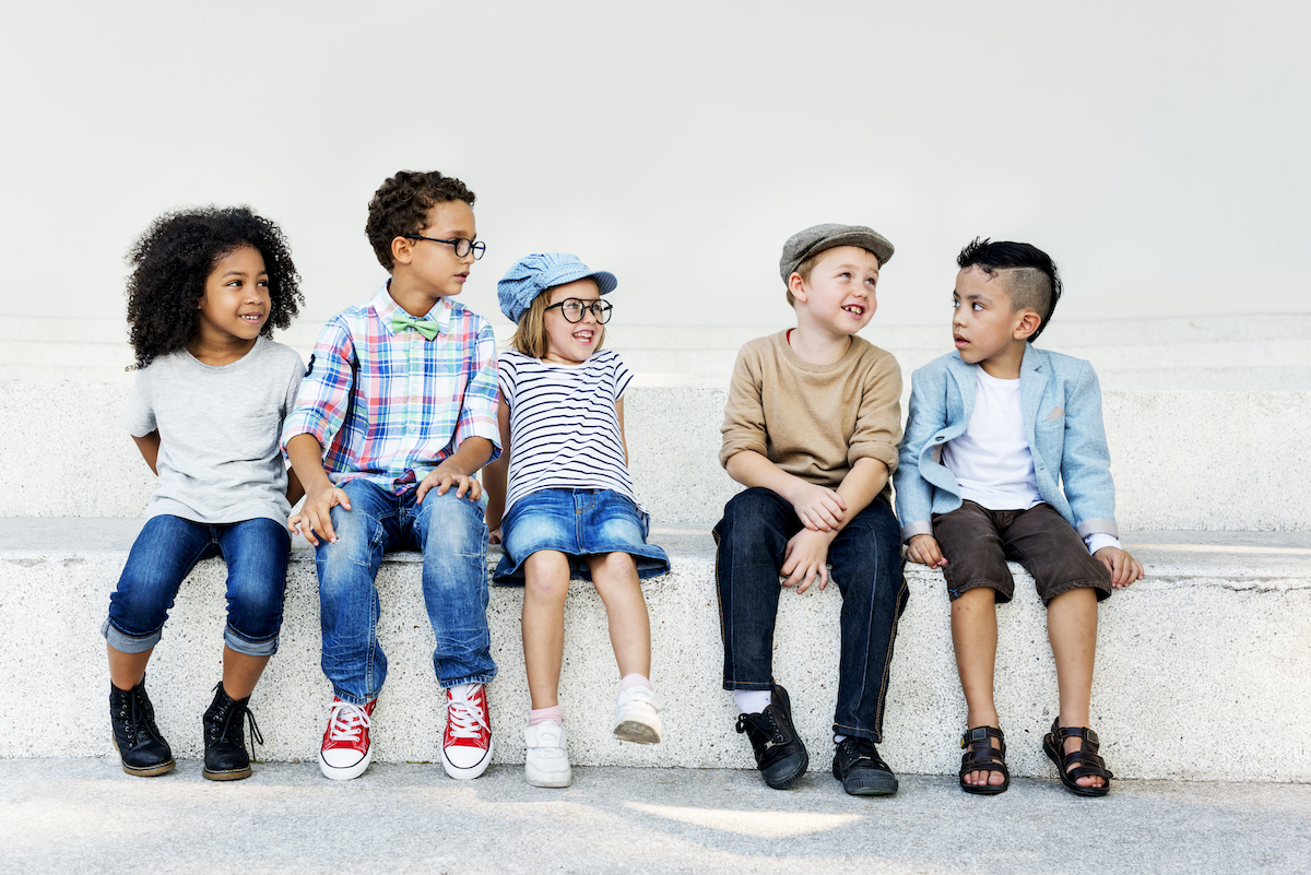 Kids seated on a bench smiling