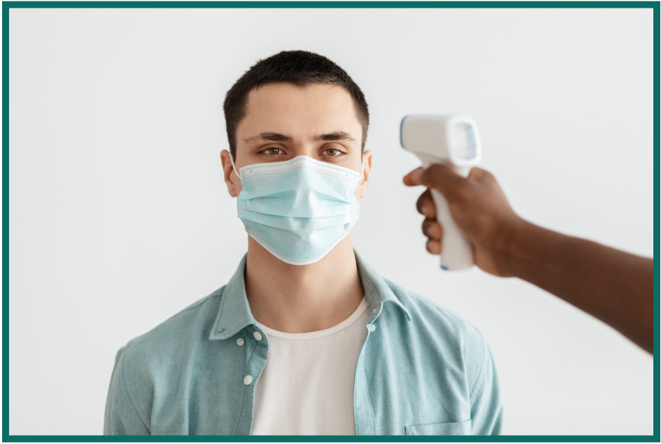 man getting his temperature taken while wearing a mask